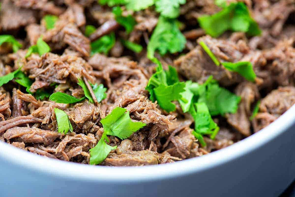 crockpot barbaco in white bowl with cilantro