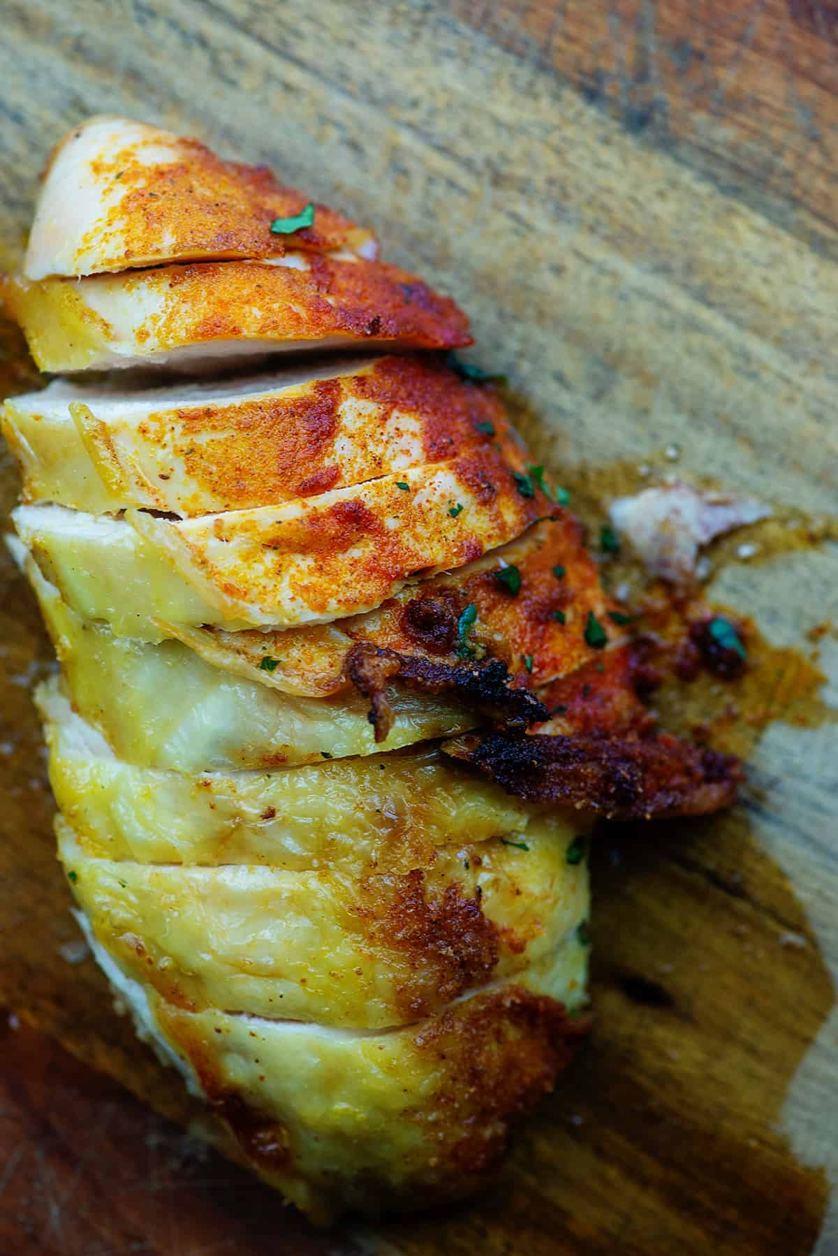 roasted chicken breasts on wooden cutting board