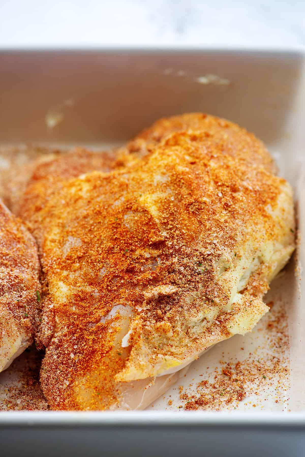chicken coated in butter and seasonings for roasting