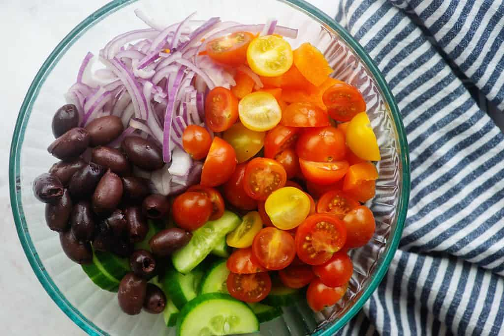 ingredients for Greek salad in glass bowl