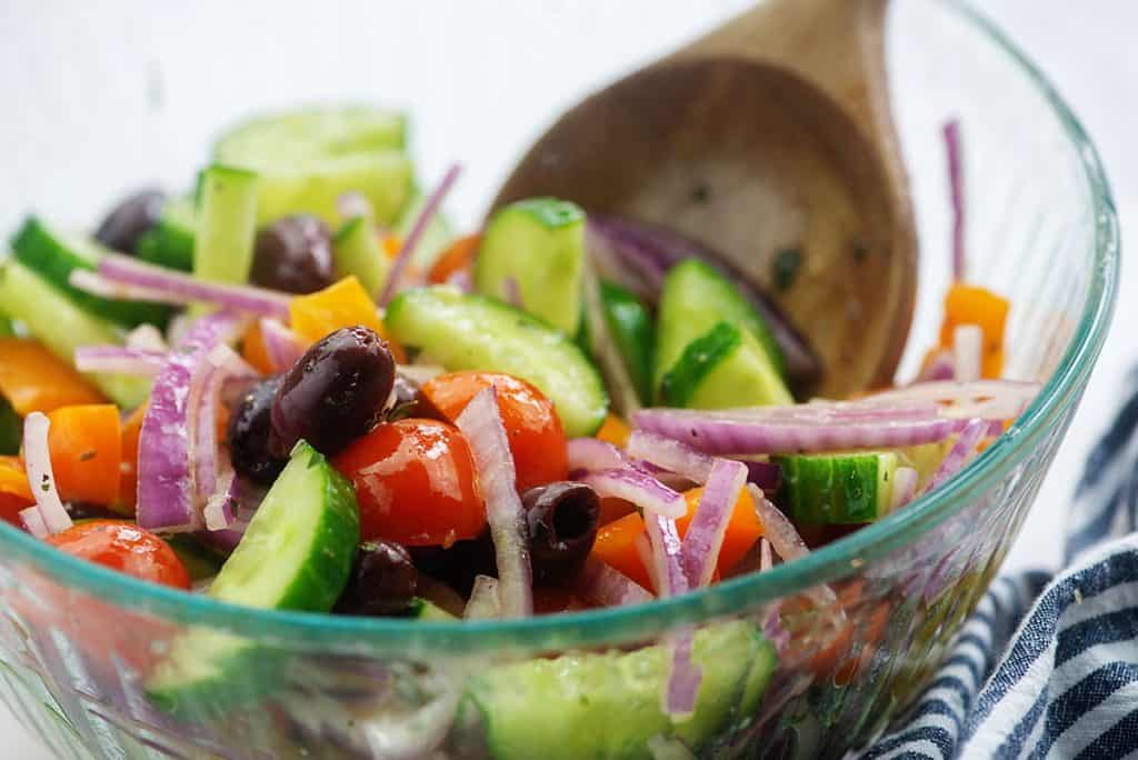Greek cucumber salad in glass bowl with dressing and wooden spoon