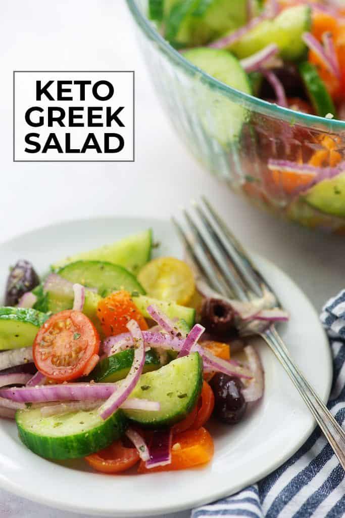 keto greek salad on white plate with blue striped napkin