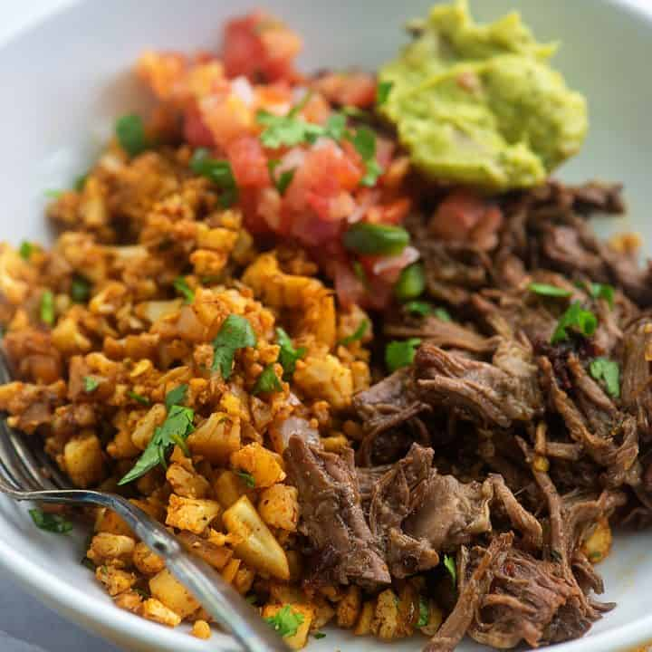 keto burrito bowl with mexican cauliflower rice and shredded beef in white bowl
