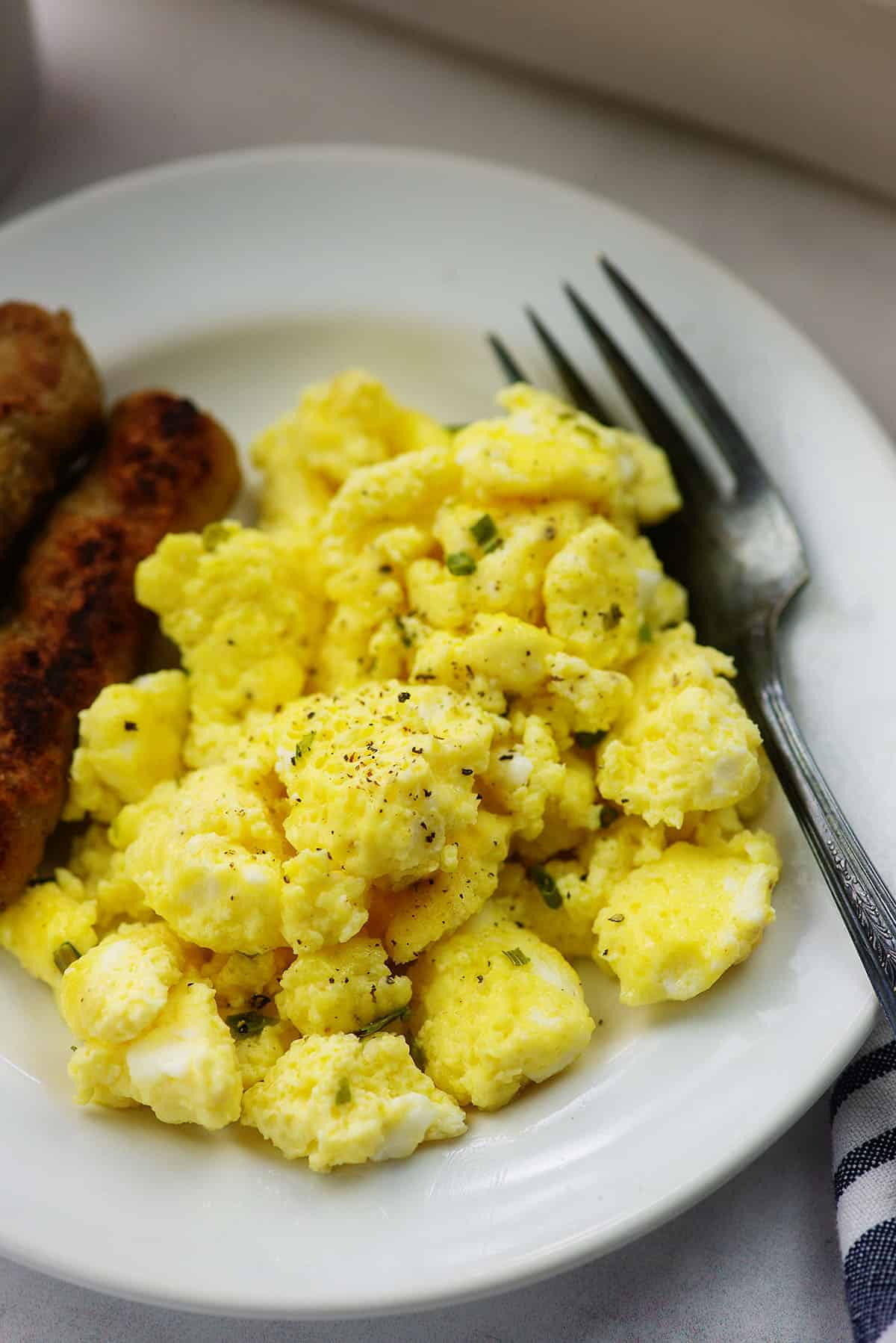 fluffy scrambled eggs on white plate with sausage links