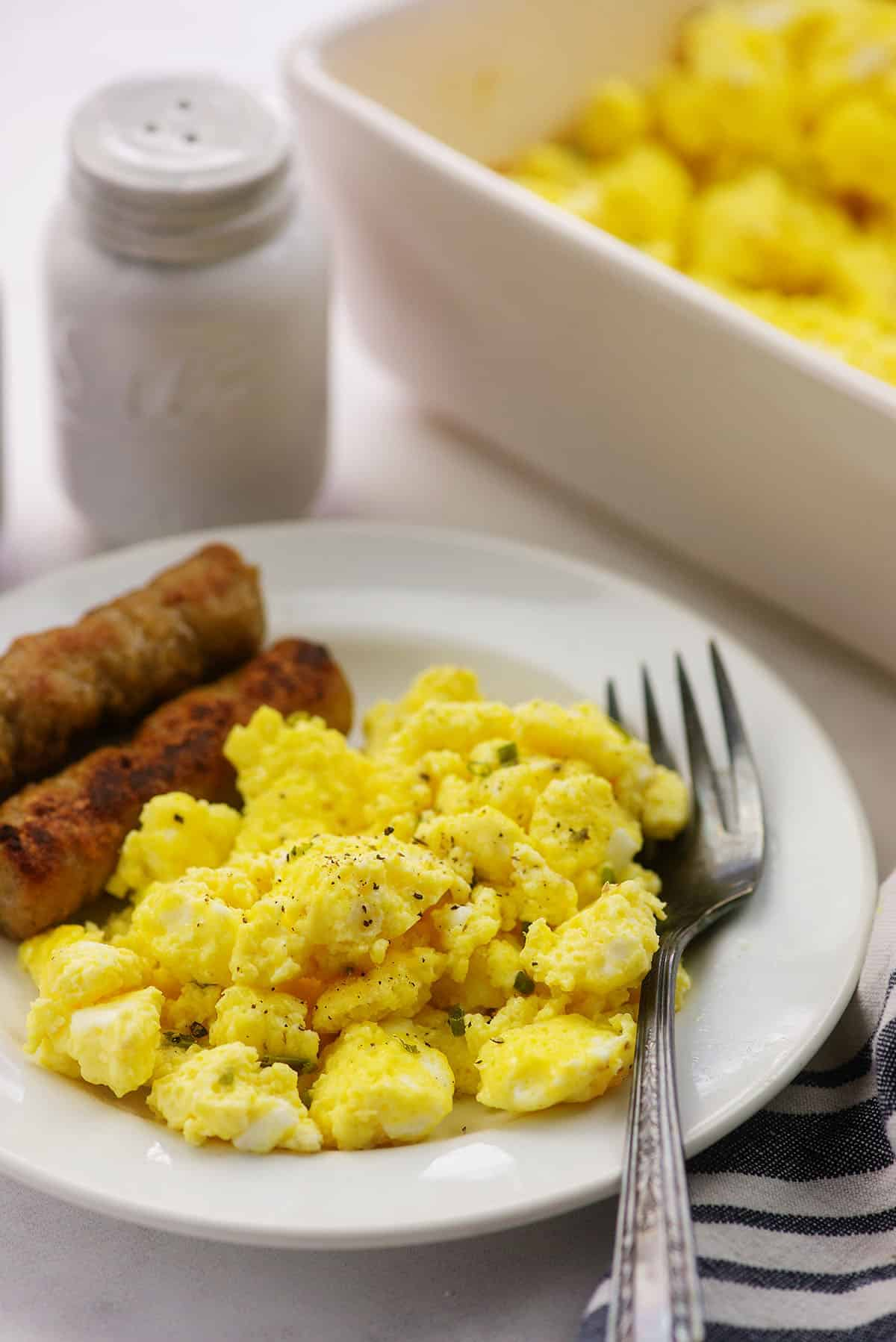 scrambled egg recipe on white plate with sausage