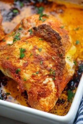 A close up of a roasted chicken breast in a white baking dish