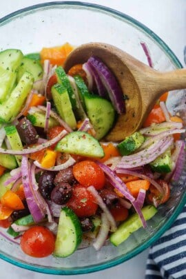 cucumbers, tomatoes, onions, and olives in glass mixing bowl