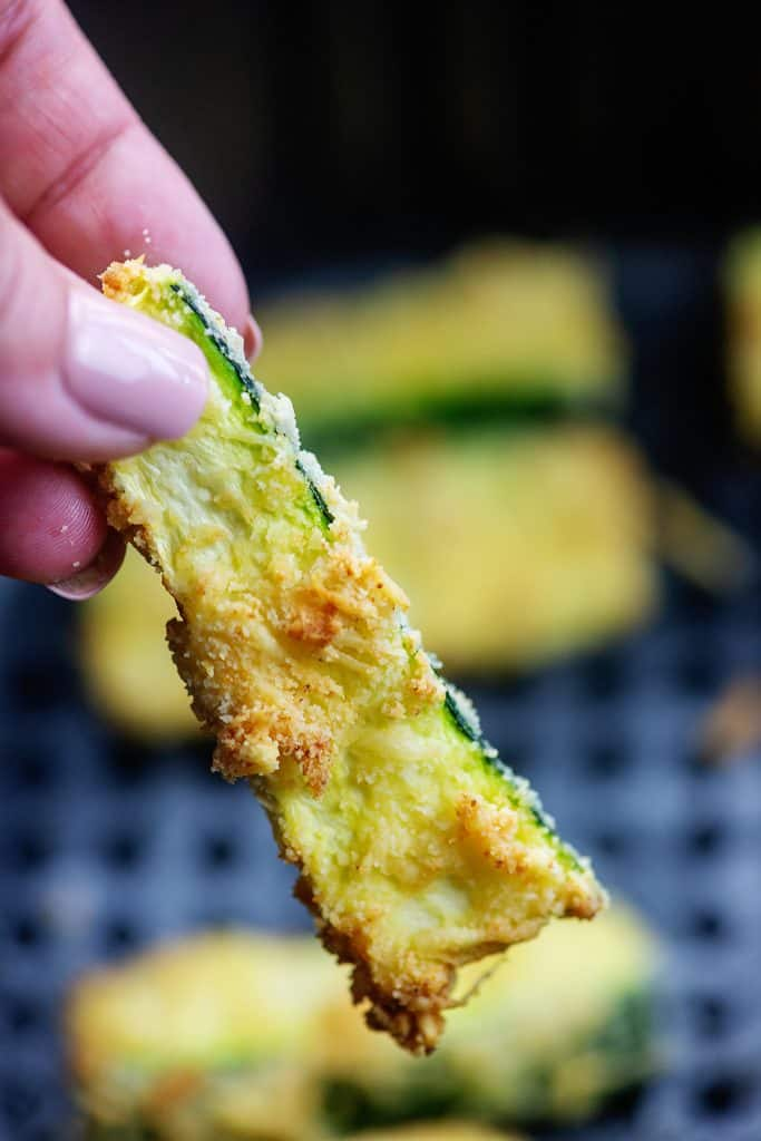 crispy zucchini fry held up over air fryer basket