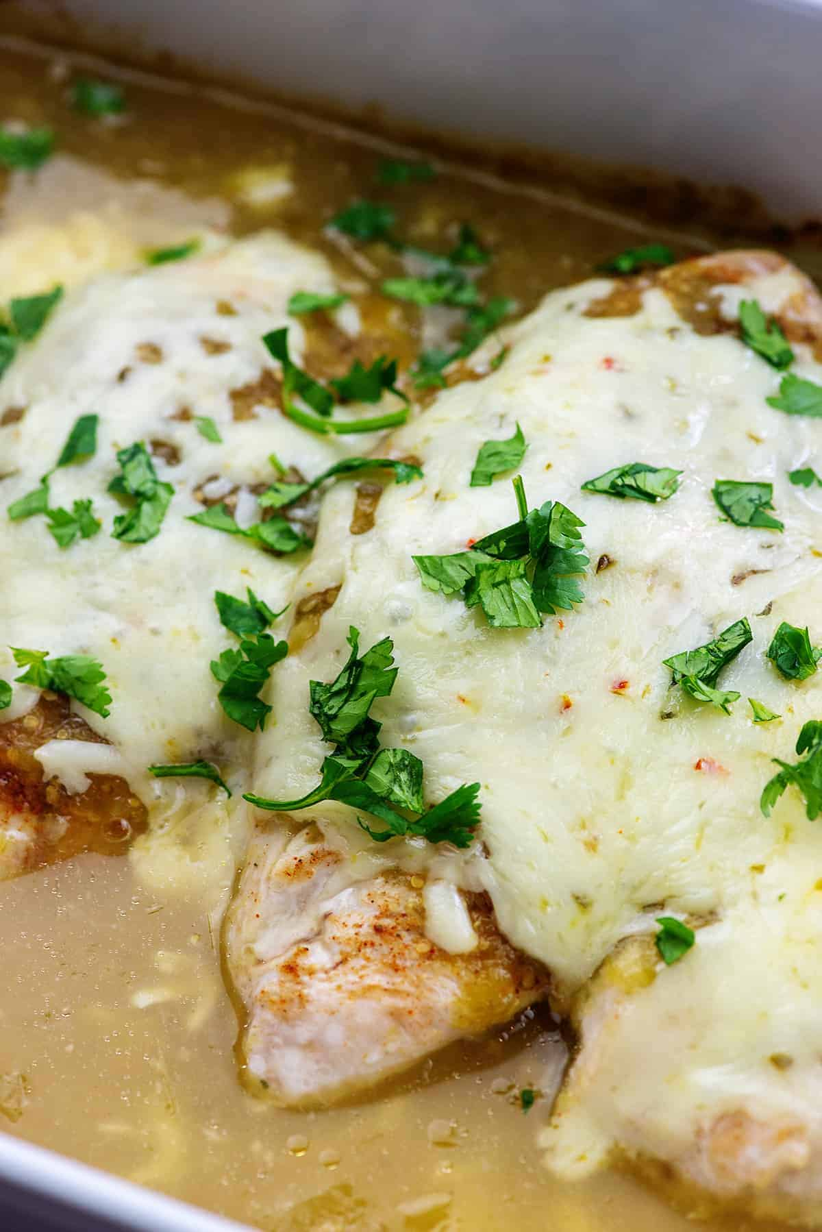 cheesy chicken baked in a dish of salsa verde