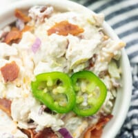 chicken salad in white bowl with jalapeno slices on top