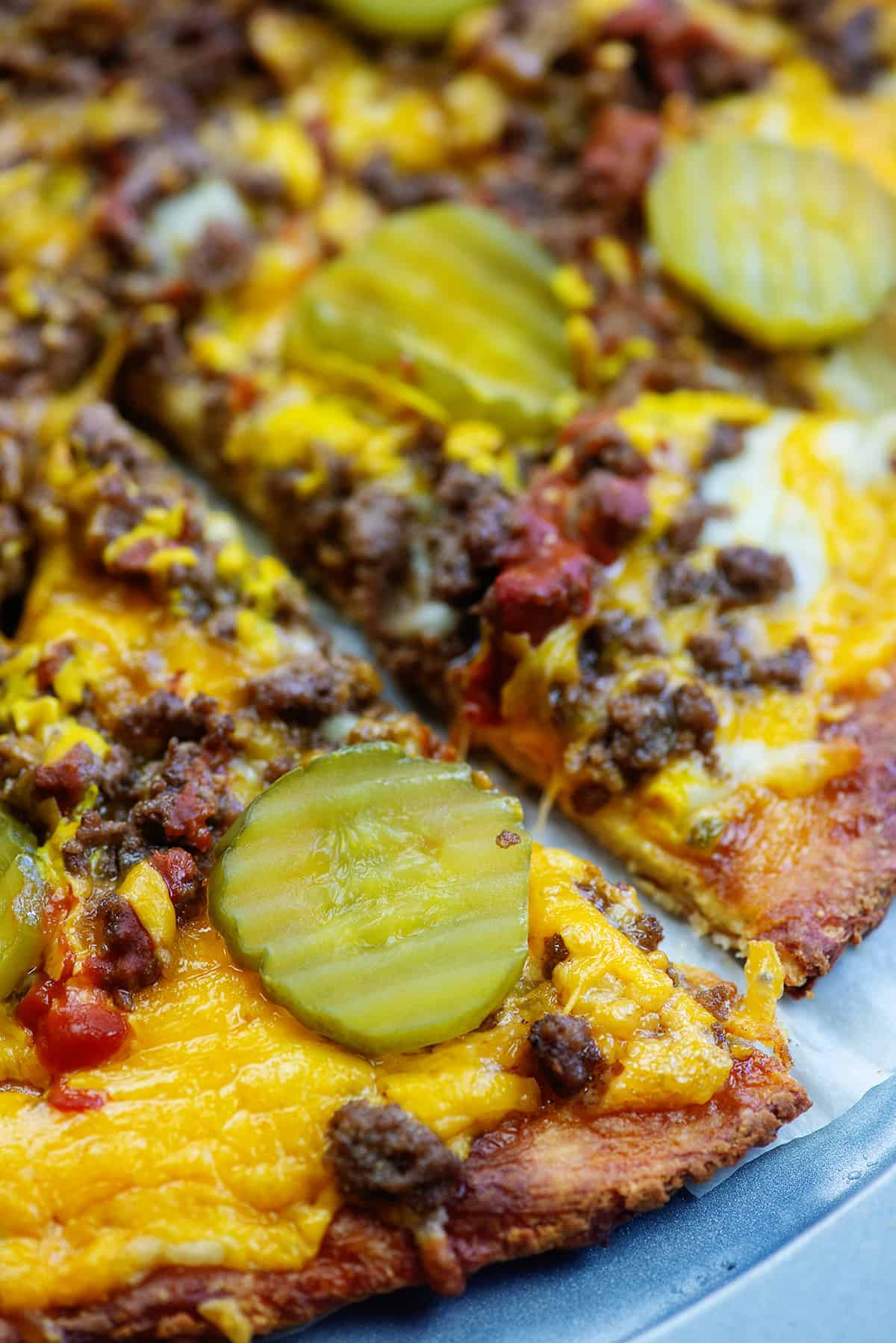 fathead pizza with ground beef, cheese, and pickles on pizza pan