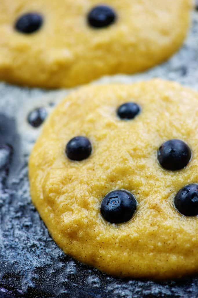 coconut flour pancakes on griddle with blueberries