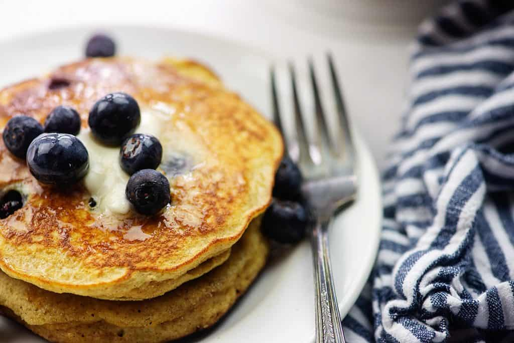 blueberry pancake recipe on white plate with vintage fork