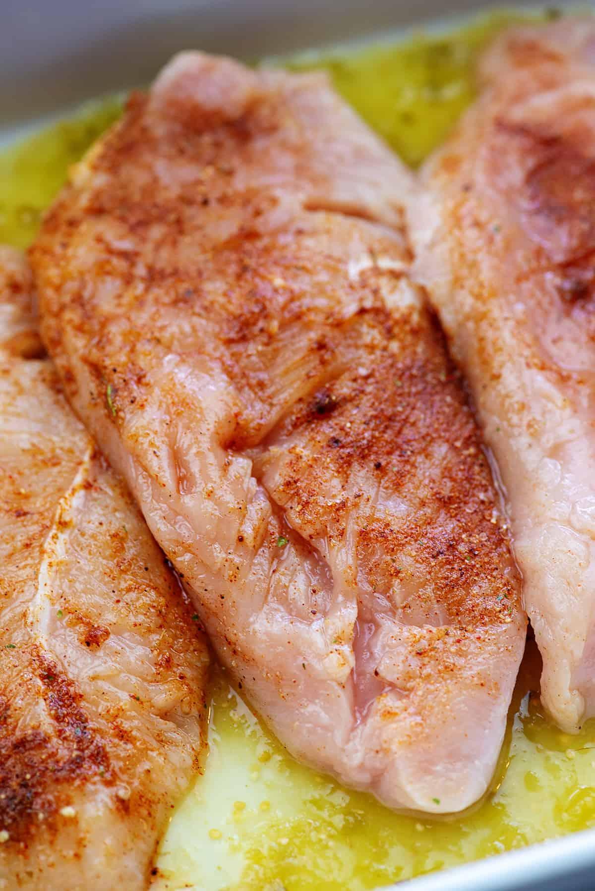 seasoned chicken breasts in white baking dish