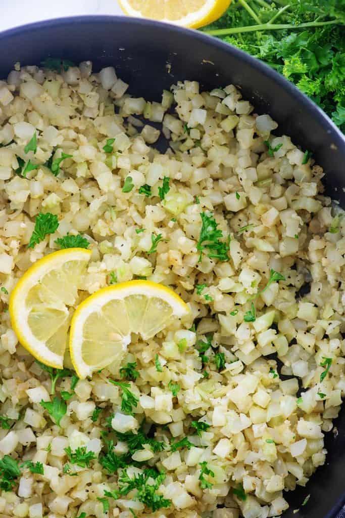 cauliflower rice in cast iron pot with lemon slices