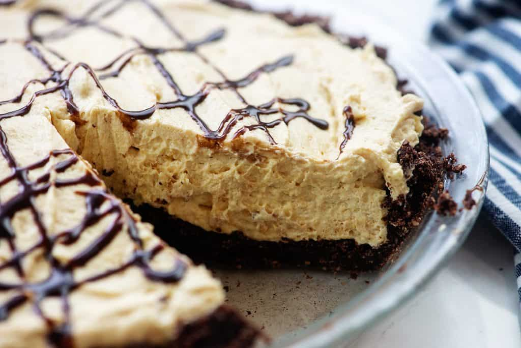 creamy low carb peanut butter pie in pie dish with chocolate drizzled on top