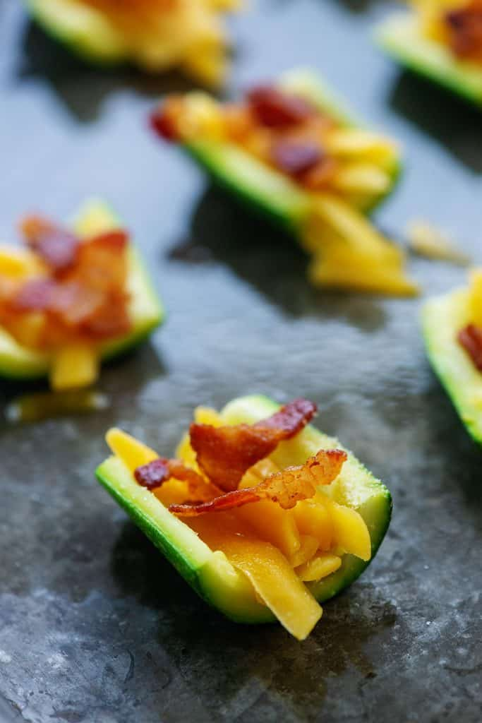 zucchini slices with cheddar and bacon on baking sheet