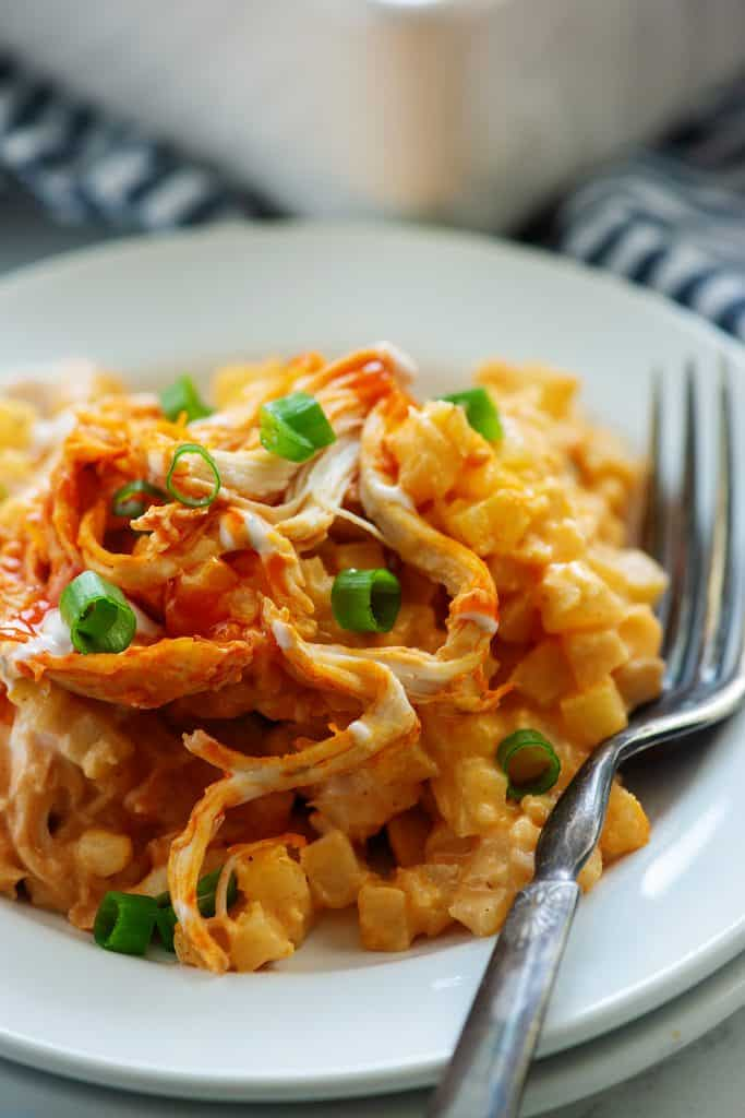 close up of buffalo chicken casserole on white plate with vintage fork