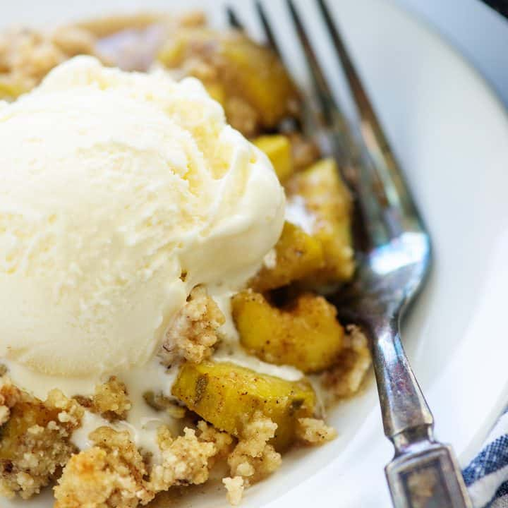 zucchini cobbler on white plate with ice cream on top