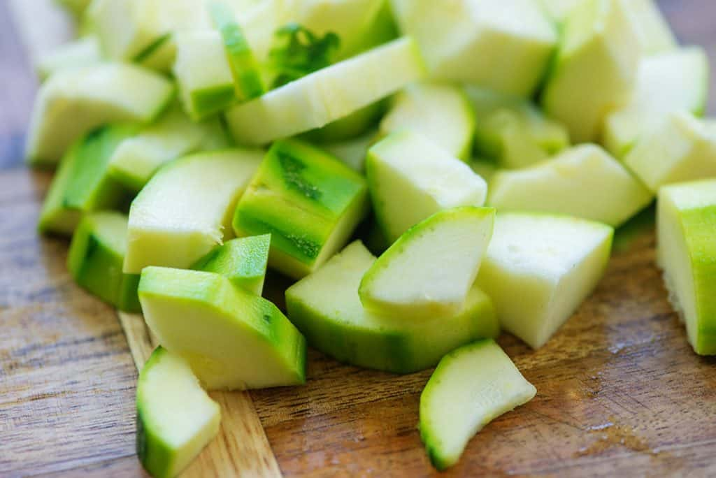 peeled and chopped zucchini on wooden cutting board