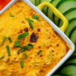 buffalo chicken dip in baking dish surrounded by fresh vegetables