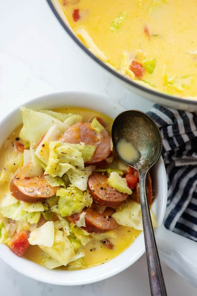 cabbage soup with sausage in white bowl next to pot of soup