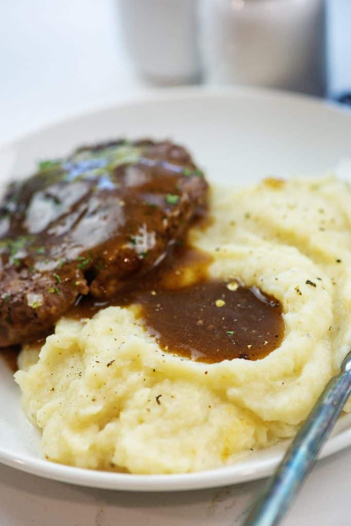 mashed cauliflower and hamburger steak topped with gravy on white plate