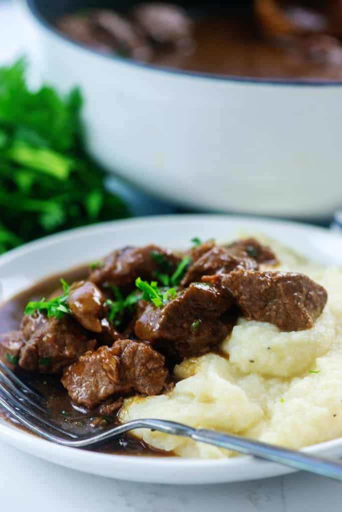 low carb beef tips on white plate with mashed cauliflower