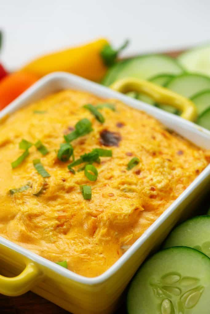 cheesy buffalo chicken dip in yellow baking dish