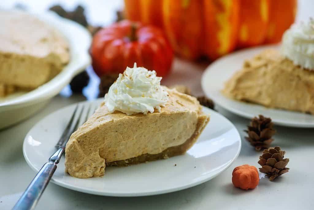 slices of keto pumpkin cream pie on white plates surrounded by pumpkins and pinecones