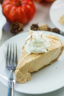 no bake pumpkin pie slice on white plate with whipped cream on top