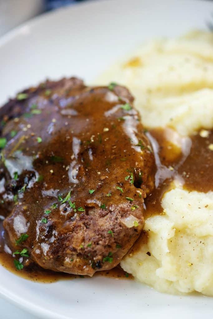 salisbury steak with gravy and mashed cauliflower on white plate