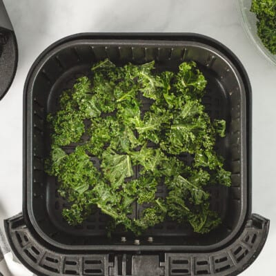 Kale chips in an air fryer basket.