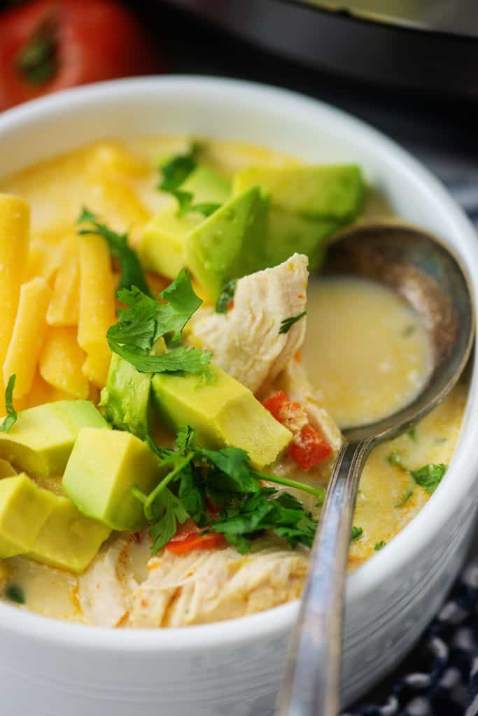 chicken fajita soup topped with avocado in white bowl with vintage spoon