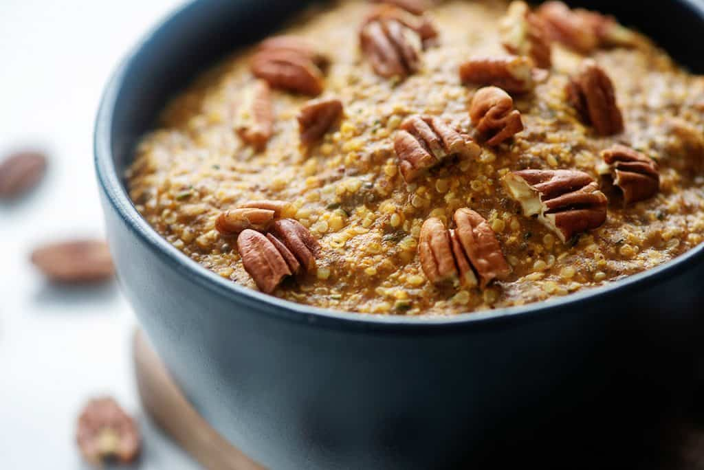 low carb oatmeal recipe topped with pecans in black bowl