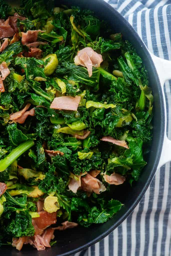 white skillet full of sauteed kale and brussels sprouts.
