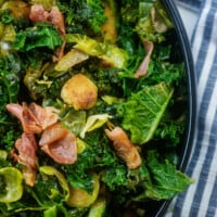 kale, Brussels sprouts, and prosciutto in black bowl by blue napkin.