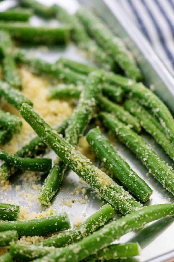 coated green beans on baking sheet.