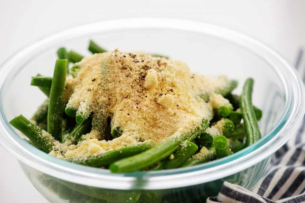 green beans and Parmesan cheese in glass mixing  bowl.