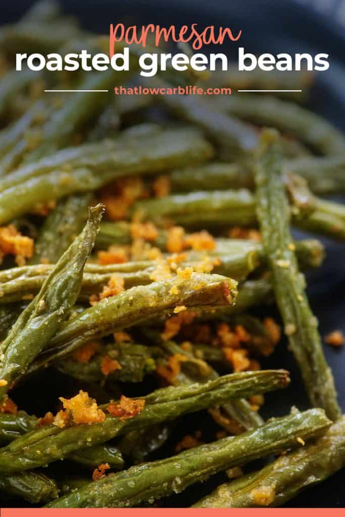 pile of roasted green beans on black plate.