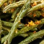 green beans coated in Parmesan on black plate.