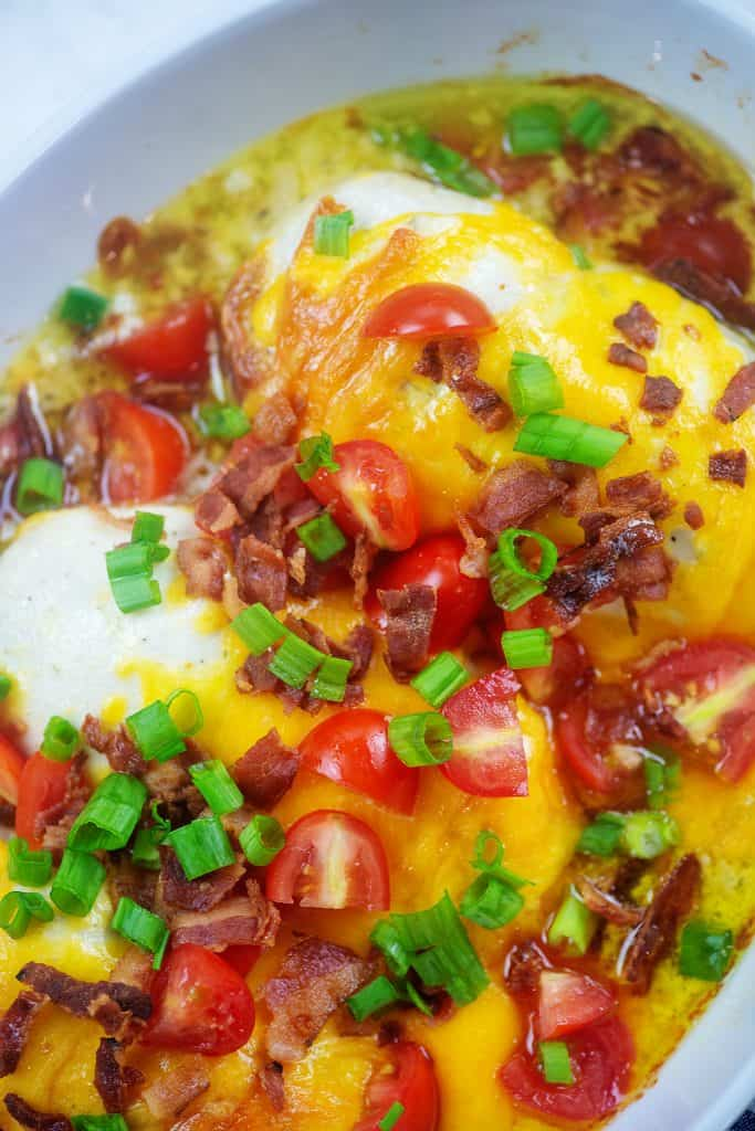 chicken in baking dish smothered with cheddar, bacon, and tomatoes.