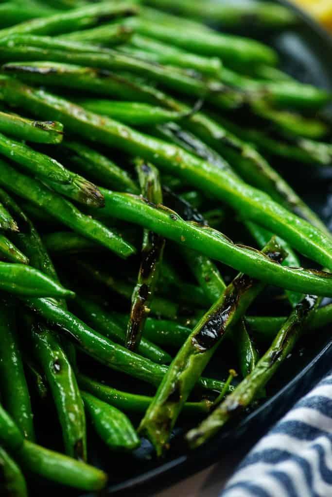blistered green beans on black plate.