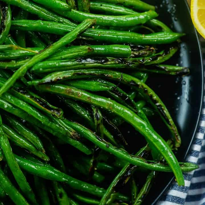charred green beans on black plate with lemon.