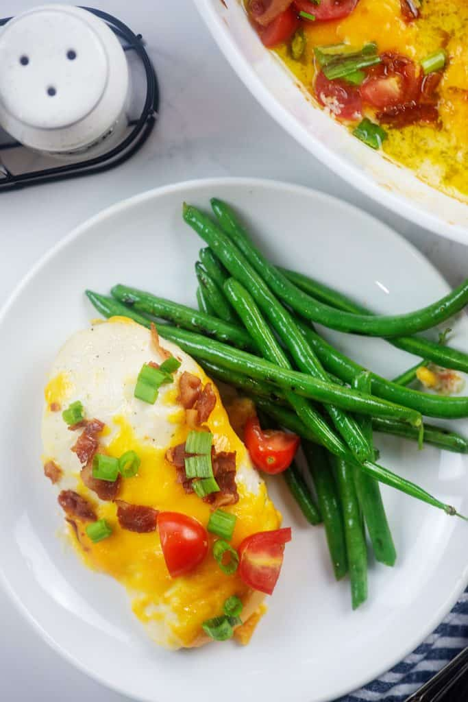 easy baked chicken topped with cheese and bacon.