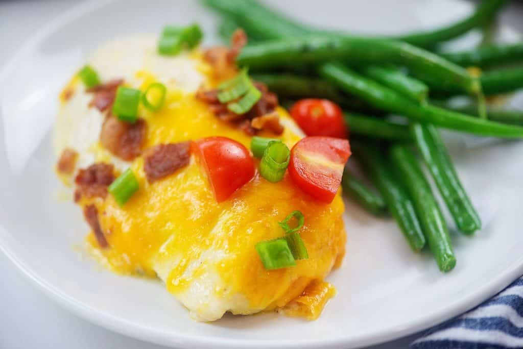 chicken breast topped with cheese and bacon on plate with green beans.