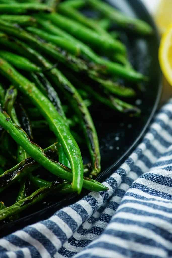 green bean recipe on black plate with striped napkin.