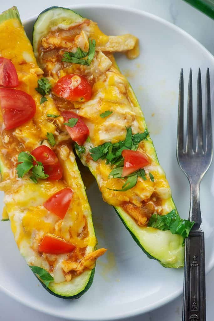zucchini boats filled with chicken enchilada mixture on white plate.