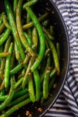 Overhead view of Szechuan green beans in black bowl.