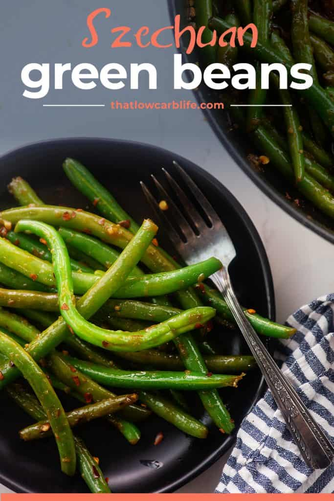 overhead view of Asian green beans on black plate.